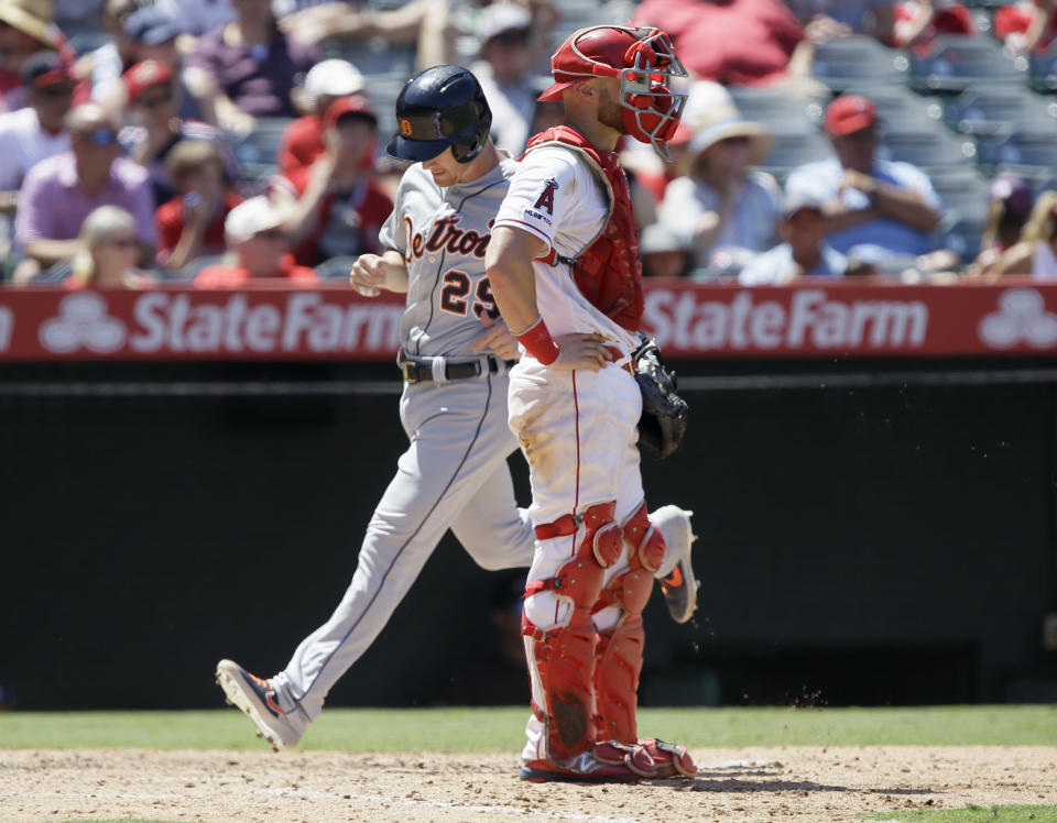 Detroit Tigers' Gordon Beckham, left, scores behind Los Angeles Angels catcher Jonathan Lucroy on a two-run single by Brandon Dixon during the fifth inning of a baseball game against the Los Angeles Angels in Anaheim, Calif., Wednesday, July 31, 2019. (AP Photo/Alex Gallardo)