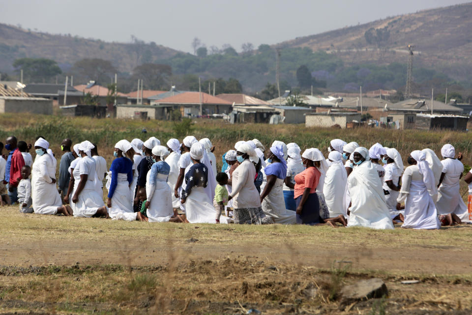Members of the Apostolic Christian Church group gather for a prayer meeting on the outskirts of the capital Harare, Sunday, Sept. 19, 2021. The Apostolic church is one of Zimbabwe's most skeptical groups when it comes to COVID-19 vaccines. Many of these Christian churches, which combine traditional beliefs with a Pentecostal doctrine, preach against modern medicine and demand followers seek healing or protection against disease through spiritual means like prayer and the use of holy water. To combat that, authorities have formed teams of campaigners who are also churchgoers to dispel misconceptions about the vaccines in their own churches. (AP Photo/Tsvangirayi Mukwazhi)
