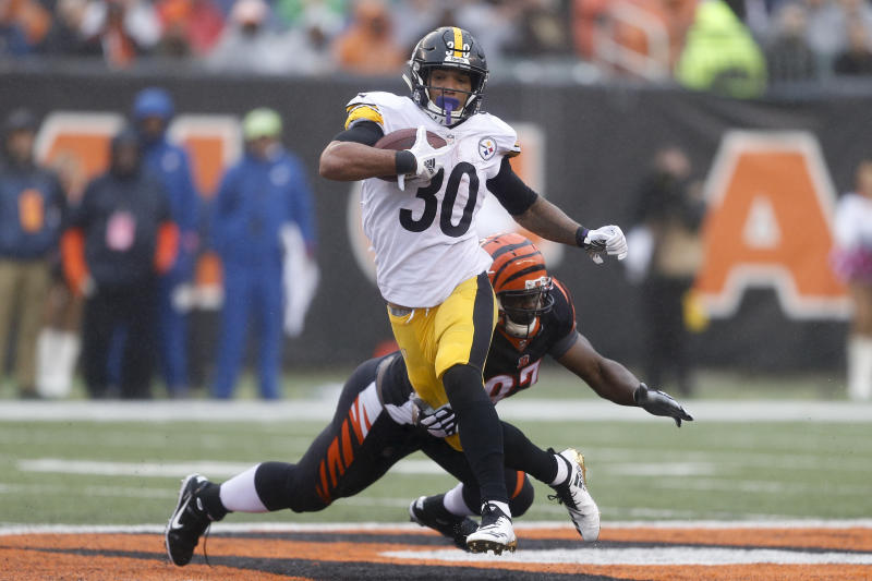 Pittsburgh Steelers running back James Conner (30) breaks away from Cincinnati Bengals defensive tackle Geno Atkins (97) in the second half of an NFL football game, Sunday, Oct. 14, 2018, in Cincinnati. (AP Photo/Gary Landers)