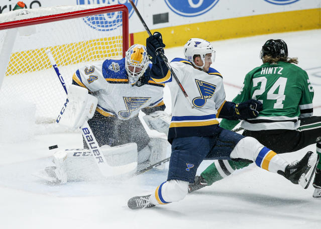 Dallas Stars forward Roope Hintz (24) attempts a backhand shot as St. Louis Blues goaltender Jake Allen (34) and forward Tyler Bozak (21) defend during the first period of an NHL hockey game game Friday, Nov. 29, 2019, in Dallas. (AP Photo/Brandon Wade)