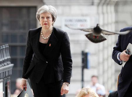 A pigeon flies ahead of Britain's Prime Minister Theresa May as she arrives at a service at St Martin-in-The Fields to mark 25 years since Stephen Lawrence was killed in a racially motivated attack, in London, Britain, April 23, 2018. REUTERS/Peter Nicholls