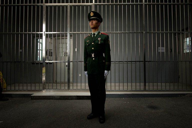 A paramilitary guard stands before the bars of a main gate to the No.1 Detention Centre in Beijing on October 25, 2012