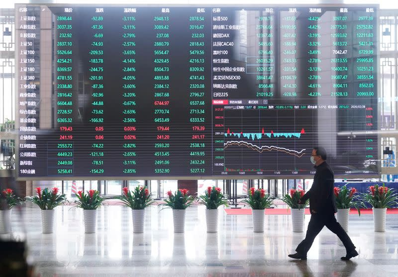 FILE PHOTO: Man wearing a face mask is seen inside the Shanghai Stock Exchange building, as the country is hit by a novel coronavirus outbreak, at the Pudong financial district in Shanghai