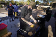 Chef Mike Winneker prepares tacos in front of his home Saturday, April 3, 2021, in Scottsdale, Ariz. Beaten down by the pandemic, many laid-off or idle restaurant workers have pivoted to dishing out food with a taste of home. Some have found their entrepreneurial side, slinging their culinary creations from their own kitchens. (AP Photo/Ross D. Franklin)