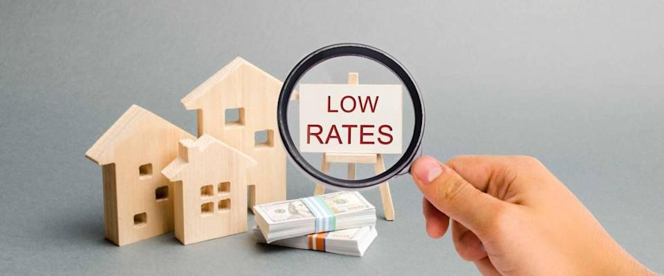 A magnifying glass is looking at a poster with the word Low rates and wooden house.