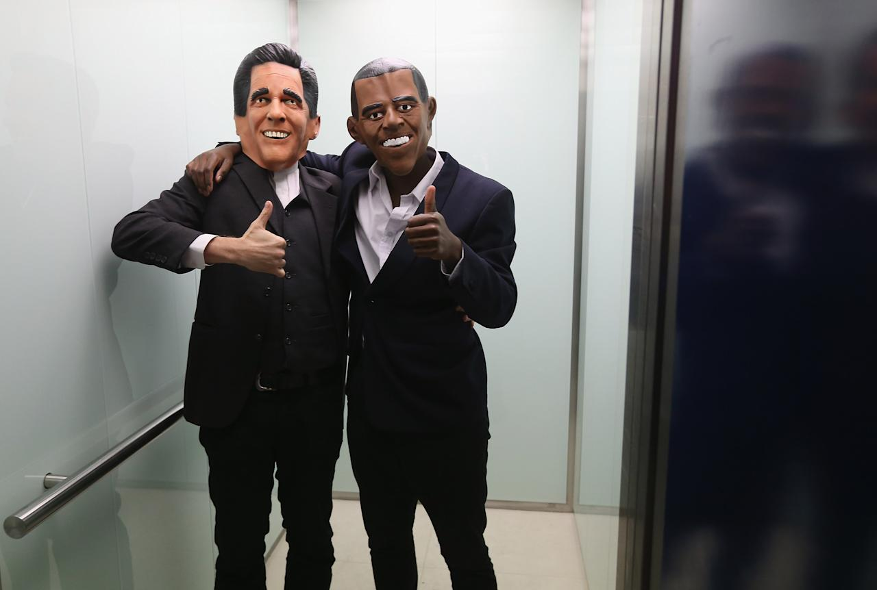 BERLIN, GERMANY - NOVEMBER 06:  Actors wearing Mitt Romney (L) and Barack Obama masks stand in an elevator while attending a U.S. election party at the Bertelsmann Foundation on November 6, 2012 in Berlin, Germany. Polls suggest today's voting in American presidential elections will create a neck and neck race between incumbent Democrat President Barack Obama and his opponent, Republican Mitt Romney.  (Photo by Sean Gallup/Getty Images)