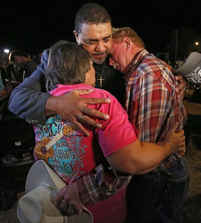 <p>Darius Johnson (C) prays with Robert Barnett (R) and his wife M.J. Barnett (L) during a vigil at the edge of town while investigators work at the scene of a mass shooting at the First Baptist Church in Sutherland Springs, Texas, Nov. 6, 2017. (Photo: Larry W. Smith/EPA-EFE/REX/Shutterstock) </p>