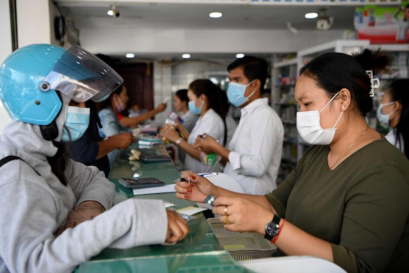 People wear face masks as they buy supplies at a pharmacy in Phnom Penh on January 29, 2020. - Cambodia's health ministry reported the country's first case of the novel coronavirus, a virus similar to the SARS pathogen on January 27: a 60-year-old man who arrived in the country from Wuhan and is now stable in an isolation room. (Photo by TANG CHHIN Sothy / AFP) (Photo by TANG CHHIN SOTHY/AFP via Getty Images)