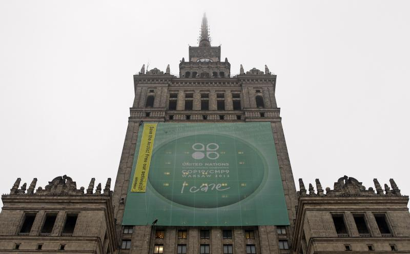 """Greenpeace activists fix a banner on the Palace of Culture and Science demanding protection of the Arctic region and the release of the so-called """"Arctic 30"""" group during the 19th conference of the United Nations Framework Convention on Climate Change (COP19) in Warsaw November 21, 2013. Three of the 30 people arrested, during a Greenpeace protest walked free on bail on Thursday, defiant that the action against Arctic oil drilling was justified and that the response by the authorities was not. REUTERS/Kacper Pempel (POLAND - Tags: POLITICS ENVIRONMENT BUSINESS)"""
