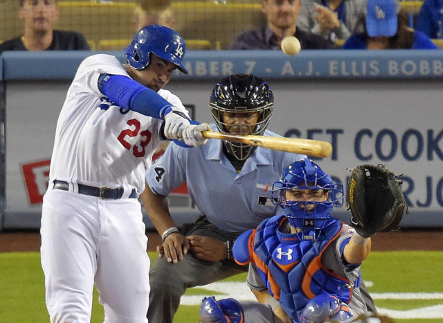 Los Angeles Dodgers' Adrian Gonzalez hits a hree-run home run in front of New York Mets catcher Travis d'Arnaud and home plate umpire CB Bucknor during the fifth inning of a baseball game, Saturday, Aug. 23, 2014, in Los Angeles. (AP Photo/Mark J. Terrill)