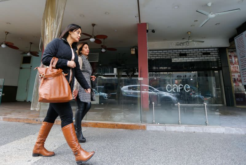 Women walk past a closed coffee shop in Beirut