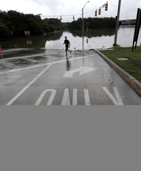 An onlooker passes along a flooded intersection, Sunday, May 26, 2013, in San Antonio. Heavy rains and flooding are being blamed for at least two deaths in San Antonio. (AP Photo/Eric Gay)