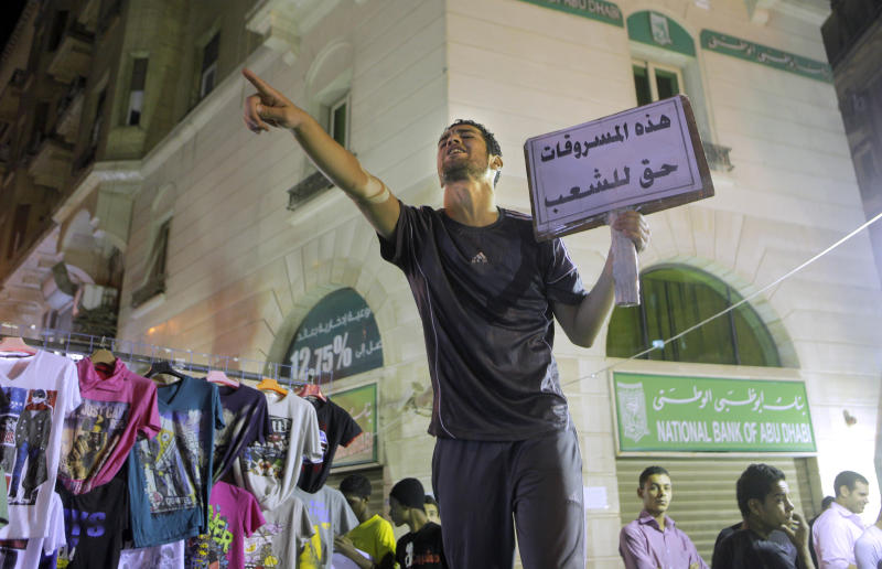 """An Egyptian vendor who sells stolen clothes at a low price calls for clients as he holds an Arabic banner reads """" those theft goods belong to people"""" marking Eid el-Fitr holiday, which caps the Muslim fasting month of Ramadan, in Cairo, Egypt late Wednesday, Aug.15, 2012. (AP Photo/Amr Nabil)"""