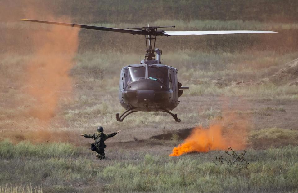 A soldier of Kazakhstan's Kazbrig brigade directs a landing Air Force Huey II helicopter during the Steppe Eagle international tactical military exercise at the Ili military range outside Almaty: Reuters