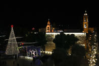 Christmas tree is lit outside the Church of the Nativity, traditionally believed by Christians to be the birthplace of Jesus Christ in the West Bank city of Bethlehem, Saturday, Dec. 5, 2020. (AP Photo/Majdi Mohammed)