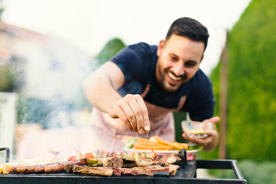 Smiling man seasoning meat on the grill
