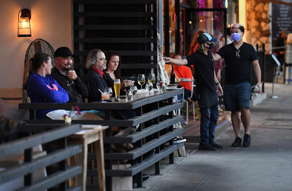 People eat on a sidewalk-facing patio outside a restaurant