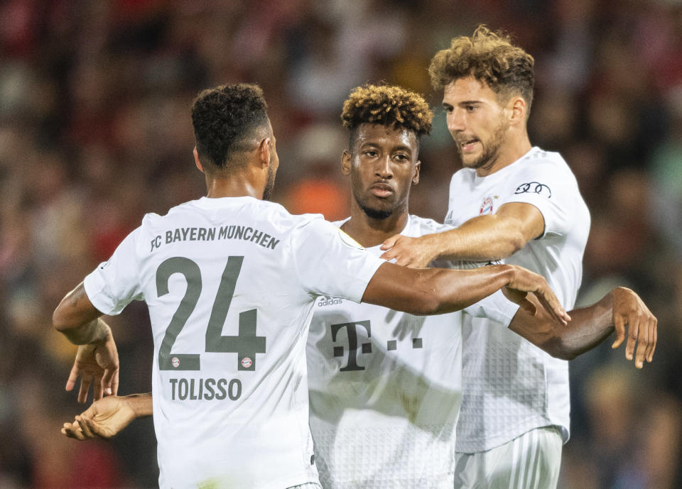 Munich's Kingsley Coman, center, celebrates with team mates Corentin Tolisso, left, and Leon Goretzka, right, after he scores his side second goal during the German soccer cup, DFB Pokal, first Round match between FC Energie Cottbus and FC Bayern Munich in Cottbus, Germany, Monday, Aug. 12, 2019. Left stand Munich's Robert Lewandowski. (Robert Michael/dpa via AP)
