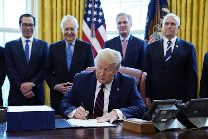 FILE - In this March 27, 2020 file photo, President Donald Trump signs the coronavirus stimulus relief package, at the White House in Washington, as from left, Treasury Secretary Steven Mnuchin, Senate Majority Leader Mitch McConnell of Ky., House Minority Kevin McCarthy of Calif., and Vice President Mike Pence, look on. Millions of Americans received government relief checks this week, and more are on the way. For some, the $1,200 payment gets them to a more comfortable place financially; for others, the money just gets them to next month. The relief payments are just one piece of a massive $2.2 trillion economic rescue package rolled out by the government to try and counter the devastating economic impacts of the coronavirus pandemic.(AP Photo/Evan Vucci)