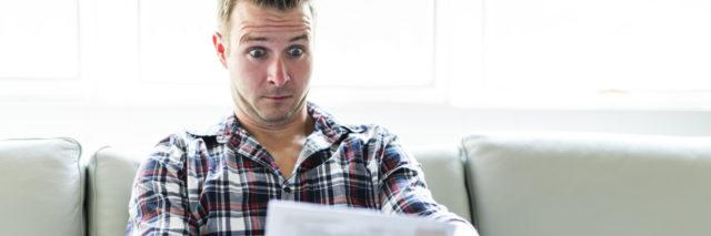 A Shocked man holding some documents in the livingroom