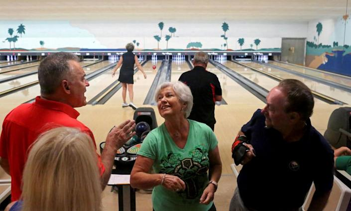 """<span class=""""element-image__caption"""">People elbow bump while bowling at Spanish Springs Town Square, in The Villages, Florida, in March.</span> <span class=""""element-image__credit"""">Photograph: Yana Paskova/Reuters</span>"""
