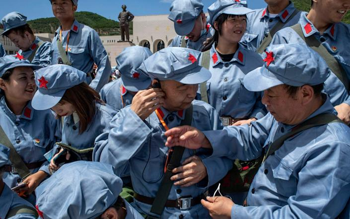 Tourists in Red Army costumes organize for a group photo at the Revolutionary Memorial Hall in Yan'an - Gilles Sabrieˆ/The New York Times/Redux/eyevine