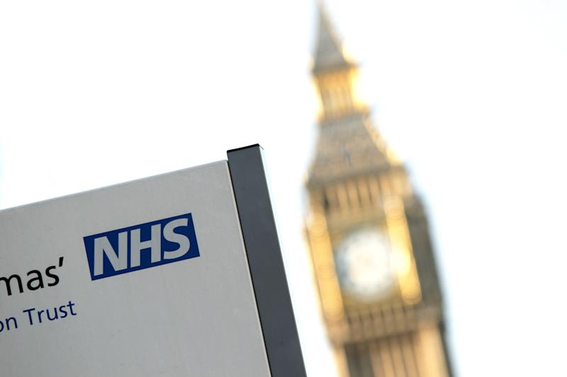 An NHS sign at St Thomas' Hospital, with Big Ben in the background, in Westminster, central London
