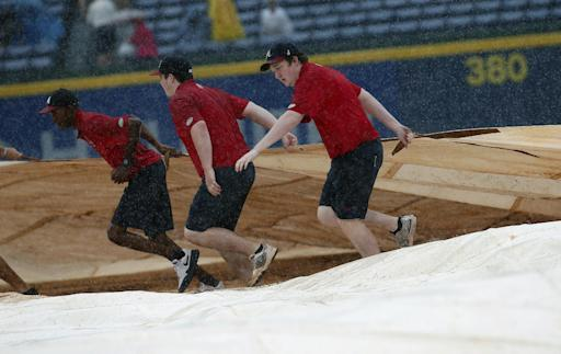 Atlanta Braves grounds crew members work to cover the infield at Turner Field during a rain shower in the sixth inning of a baseball game against Philadelphia Phillies in Atlanta, Sunday, July 20, 2014. (AP Photo/John Bazemore)