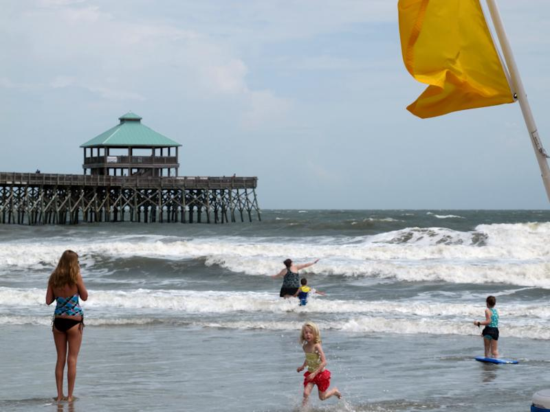 Swimmers play at the edge of the surf beneath a yellow caution flag at Folly Beach, S.C., on Tuesday, May 29, 2012. The National Hurricane Center forecasts the remnants of Tropical Storm Beryl will strengthen and reach tropical storm strength off the South Carolina coast on Wednesday. (AP Photo/Bruce Smith).
