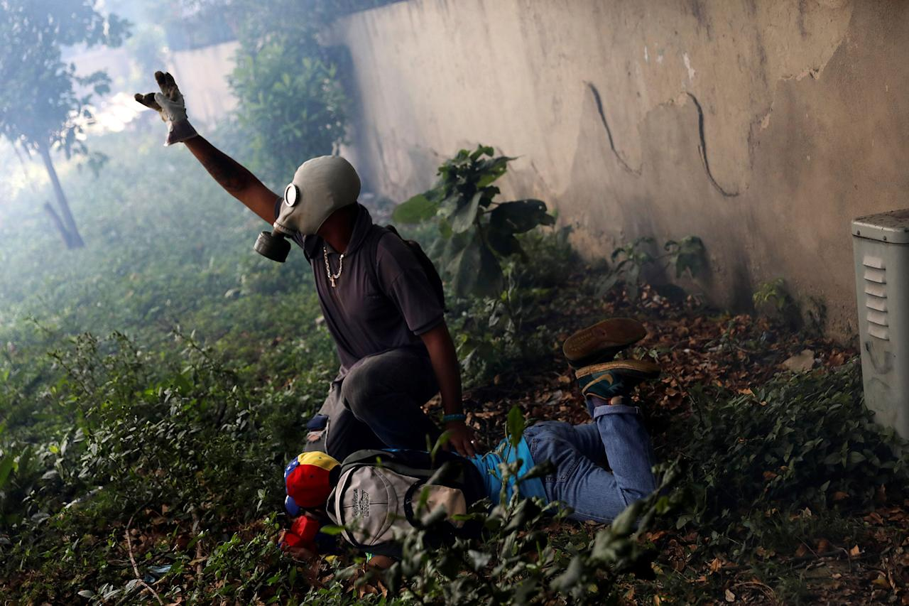 "<p>An injured demonstrator is helped by another protester after clashing with riot police during the ""mother of all marches"" against Venezuelan President Nicolas Maduro in Caracas, Venezuel April 19, 2017. (Carlos Garcia Rawlins/Reuters) </p>"