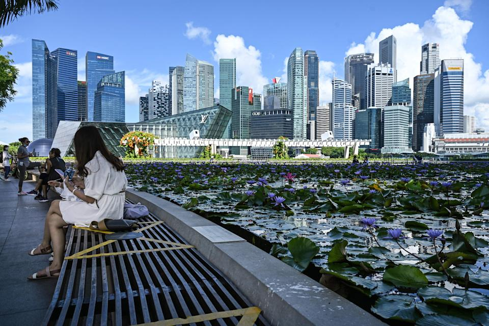 People sitting next to a pond with the view of Singapore's CBD skyline in the background. (PHOTO: Getty Images)