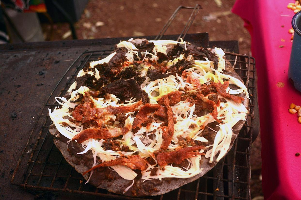 tlayuda being cooked in the stove or anafre in mexico, delicious huge tortilla with beans, oaxaca cheese and jerky beef
