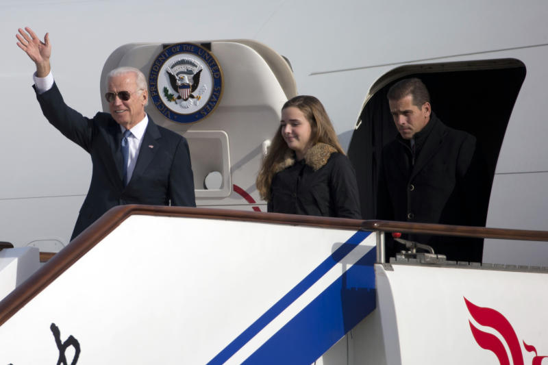 """U.S. Vice President Joe Biden (L) waves as he walks out of Air Force Two with his granddaughter Finnegan Biden and son Hunter Biden at the airport in Beijing December 4, 2013. Biden should not expect to make much progress in defusing tensions over the East China Sea if he plans to repeat """"erroneous and one-sided remarks"""" on the issue when he visits China, a top state-run paper said on Wednesday. Beijing's decision to declare an air defence identification zone in an area that includes disputed islands has triggered protests from the United States, Japan and South Korea and dominated Biden's talks in Tokyo on Tuesday. REUTERS/Ng Han Guan/Pool (CHINA - Tags: POLITICS)"""
