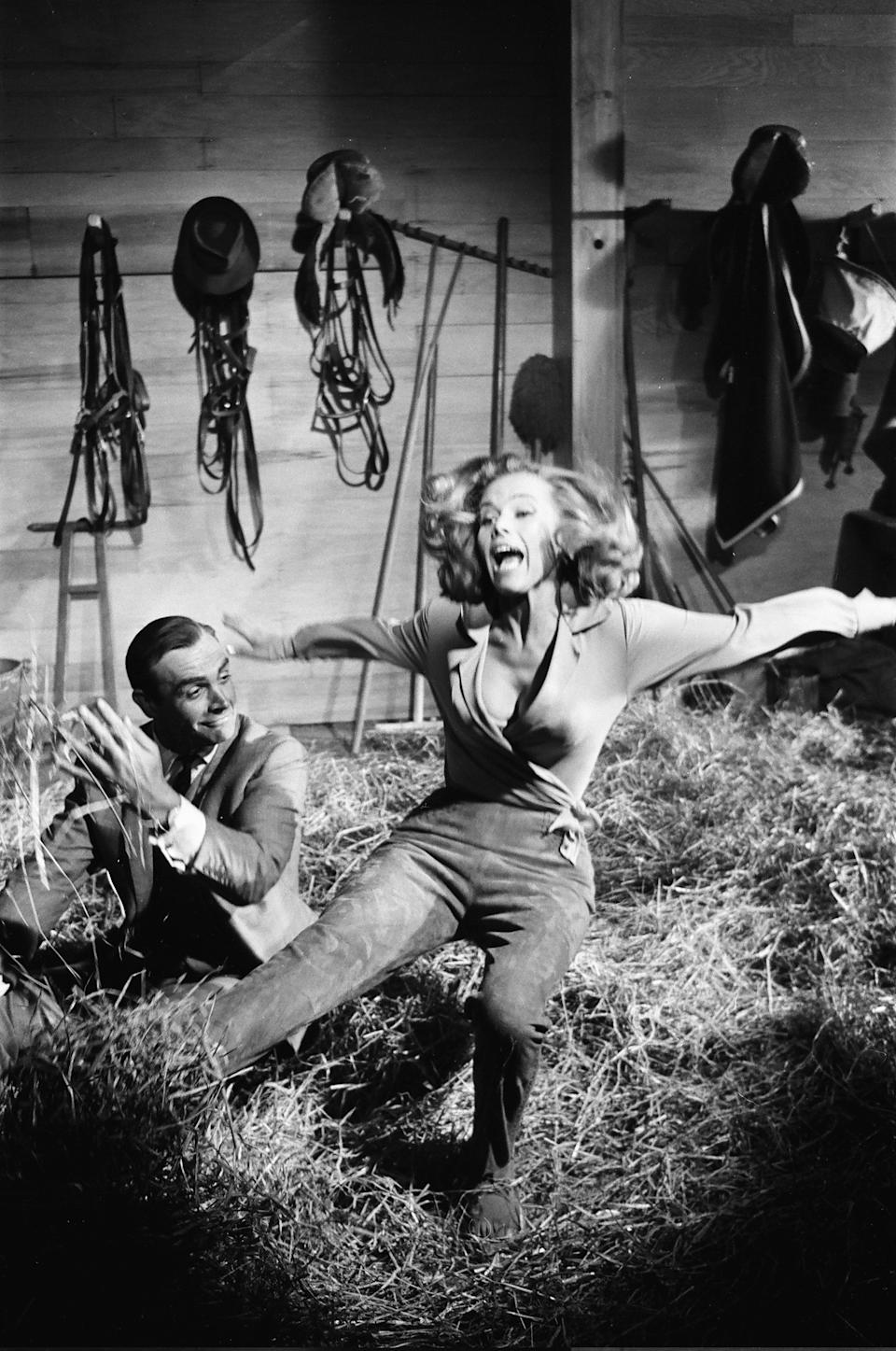 Honor Blackman as Pussy Galore and Sean Connery as James Bond seen here filming a fight scene which develops into a love scene in Goldfingers barn on the Pinewood studios back lot, 2nd June 1964. (Photo by Victor Crawshaw/Mirrorpix/Getty Images)