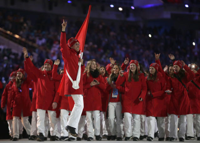 Simon Ammann of Switzerland carries the national flag as he leads his team into the stadium during the opening ceremony of the 2014 Winter Olympics in Sochi, Russia, Friday, Feb. 7, 2014. (AP Photo/Matt Dunham)