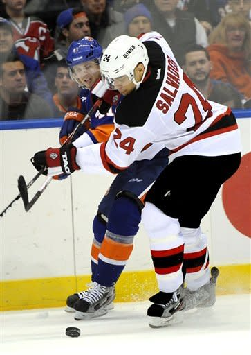 New York Islanders' David Ullstrom (41) and New Jersey Devils' Bryce Salvador (24) battle for the puck in the second period of an NHL hockey game on Saturday Jan., 19, 2013 at Nassau Coliseum in Uniondale, N.Y. (AP Photo/Kathy Kmonicek)