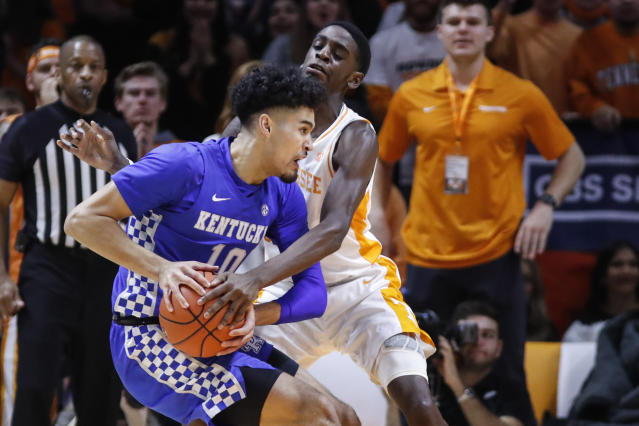 Kentucky guard Johnny Juzang (10) works for a shot as Tennessee guard Davonte Gaines (0) defends during the first half of an NCAA college basketball game Saturday, Feb. 8, 2020, in Knoxville, Tenn. (AP Photo/Wade Payne)