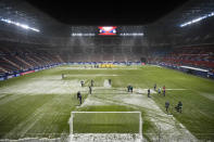 Workers clear snow from the pitch before the start of a Spanish La Liga soccer match between Osasuna and Real Madrid at El Sadar stadium in Pamplona, Spain, Saturday, Jan. 9, 2021. (AP Photo/Alvaro Barrientos)