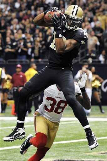 New Orleans Saints wide receiver Marques Colston (12) pulls in a touchdown reception over San Francisco 49ers free safety Dashon Goldson (38) in the first half of an NFL football game in New Orleans, Sunday, Nov. 25, 2012. (AP Photo/Bill Feig)