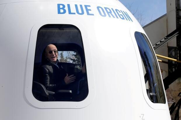 Amazon and Blue Origin founder Jeff Bezos is shown at a 2017 event in Colorado showing a mockup of the New Shepard rocket booster and capsule.   (Isaiah J. Downing/Reuters - image credit)