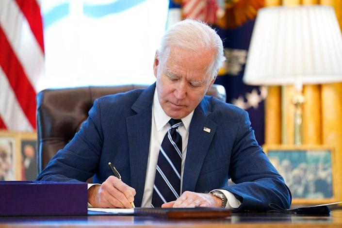 President Joe Biden signs the American Rescue Plan into law in the Oval Office of the White House on March 11. The measure includes incentives for states that have not expanded their Medicaid programs.