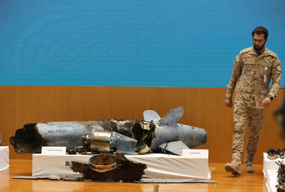A Saudi military officer walks next to what was described a misfired Iranian cruise missile used in an attack this weekend that targeted the heart of Saudi Arabia's oil industry, during a press conference of military spokesman Col. Turki al-Malki in Riyadh, Saudi Arabia, Wednesday, Sept. 18, 2019. Though Yemen's Houthi rebels claimed the assault, the U.S. alleges Iran was behind it. (AP Photo/Amr Nabil)