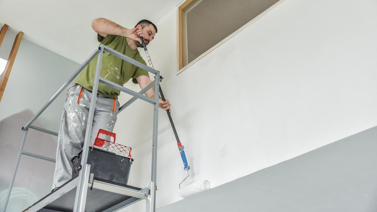 Profesional painter painting with paint roller.