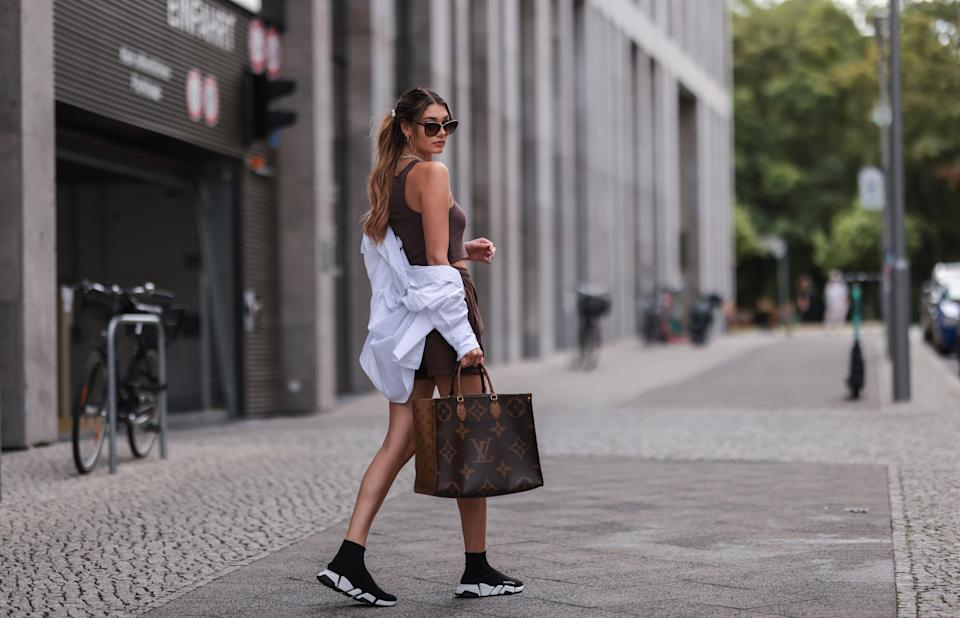 BERLIN, GERMANY - AUGUST 03: Sarah Posch wearing Louis Vuitton brown Monogramm On the Go bag, Balenciaga black sneaker, Worst Behavior brown shorts, Zara white top and Bruna gold earrings on August 03, 2021 in Berlin, Germany. (Photo by Jeremy Moeller/Getty Images)
