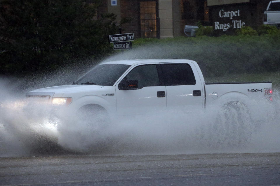 A pickup truck travels along a flooded road as severe weather produces torrential rainfall, Tuesday, May 4, 2021 in Vestavia, Ala. (AP Photo/Butch Dill)
