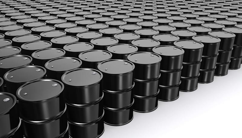 Rows of black oil barrels on a white floor.
