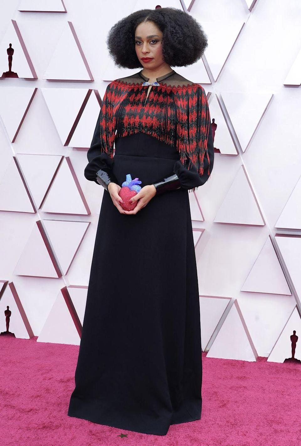 <p>Wearing a quirky patterned black gown with a crystal encrusted heart clutch.</p>