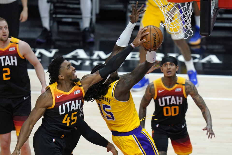 Utah Jazz guard Donovan Mitchell (45) blocks a shot by Los Angeles Lakers center Montrezl Harrell (15) during the first half of an NBA basketball game Wednesday, Feb. 24, 2021, in Salt Lake City. (AP Photo/Rick Bowmer)