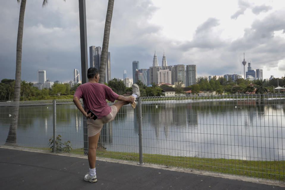 A man is seen stretching at the Titiwangsa lake park in Kuala Lumpur May 4, 2020. — Picture by Shafwan Zaidon