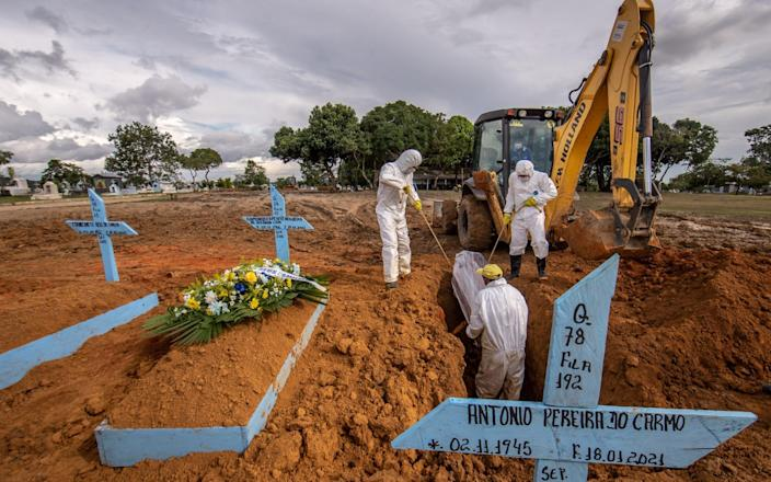 Workers wearing personal protective equipment (PPE) lower the casket of a Covid-19 victim into a grave at a cemetery in Manaus, Brazil